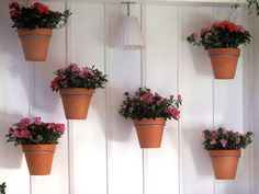 Vertically mounted flower pots create a charming spot for more gardening.