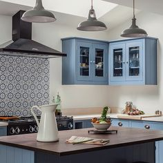 This kitchen by British Standard puts a modern twist on Shaker style. with bright blue cupboards and a splashback of patterned tiles