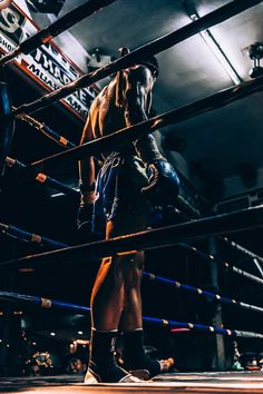 A male fighter standing in the ring wearing boxing gloves in Chiang Mai