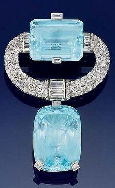 An Art Deco aquamarine and diamond brooch, circa 1930. The cushion-shaped aquamarine drop to a pavé old brilliant-cut 'c' scroll surmount with baguette diamond detail incorporating a single cut-cornered rectangular aquamarine. #ArtDeco #brooch