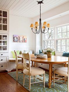 Built-in banquette seating provides plenty of room for a crowd in this cozy breakfast nook. A large built-in cabinet along one wall of the dining area offers convenient storage space for dishware, placemats, and more. The gol