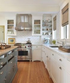Beautiful classic two-tone kitchen with white glass-front kitchen cabinets with marble countertops, subway tiles backsplash, blue gray kitchen island with lots of storage & butcher block countertop, stainless steel floating shelves and bamboo roman shades