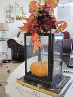 My lantern all dressed up for fall.  Use what you have, move things around for a fresh take. I added a darling little pumpkin and a bit of fall foliage and a quick bow to top it.