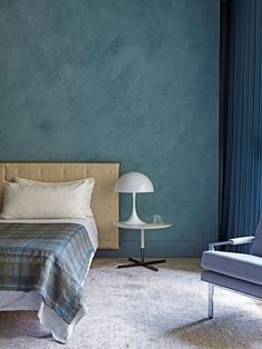"""I wanted the master bedroom to have moments of richness, so we wrapped the wall in a blue-green plaster,"" says Frampton. ""The space is quite large, and having one dark wall was important to having it relate to the rest of the home."" Both the leather-and-linen–clad headboard and the small side table are from Poltrona Frau. The plaid linen bed cover is by Angela Brown Ltd."