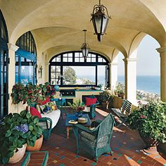 You hardly notice the kitchen components on this patio―and that's a good thing. The cooking area doesn't detract from the Mediterranean style or take up too much space.  • Use plate-glass and crank-out casement windows to protect cooks from wind and rain without obstructing the view.    • Incorporate punches of color to energize a neutral space. Here, vintage wicker furniture was painted a vibrant green to coordinate with the accent floor tiles.     CoastalLiving.com