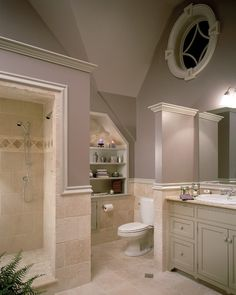 Beautiful organized bathroom.  The shelfs tucked into the wall studs is clever.  The 3/4 wall that separates the sink from the toilet adds privacy.