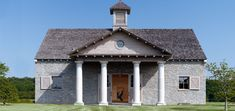 Barn in Kentucky horse-breeding country by Ken Tate Architect. Tate drew inspiration from the portico of Inigo Jones' Covent Church in London for simple Tuscan columns that support a pediment with a round oculus.