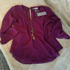 "Jennifer Lopez Sparkly Days Top 100% polyester, sheer top in ""Fun Plum"". It is a loose fit shirt, with a split, fly away back outer layer. It has a diamond button on the back at the top of the neck, and has a v-neck. Comes with the extra button, in perfect condition. Note: shirt material is not sparkly, despite the title of the shirt, it is referring to button on back :) any questions, please ask!   Offers welcome! Jennifer Lopez Tops Blouses"