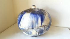 This piece measures approximately 9 tall, 9 in diameter and has a tiny .25 opening. It is in excellent vintage condition with no chips, cracks or repairs. This incredible, organic American Raku vase is early work by award winning, Seattle artist John Fleming, under the tutelage of Paul Soldner in the 1970s. It features indigo drip glaze over white, with an abstract crackle finish and accents of golden brown.  ABOUT JOHN FLEMING: I have spent 30 years developing a broad portfolio of art…