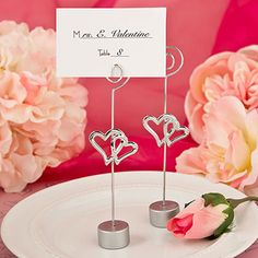 Two hearts are a must for any romantic occasion and these place card holders make a perfect piece!Love is in the air and our fabulous holders will bring the message directly onto your event tables. Stunning in shiny silver, they make perfect placecard holders to welcome your guests.Our placecard holder is made from silver metal wire and features two gorgeous silver metal intertwined heart charms. The round base is made from poly resin and finished in a matching silver color.The coiled top…