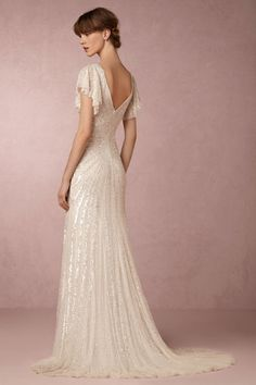 Cibella Gown-- Evoking the romantic spirit of fashion's golden age, iridescent beadwork steals the show in a subtle pattern which begins with flutter sleeves, converges at the waist (for a slimming effect), and continues down to a floor-skimming hemline and generous train.