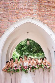 bride and her bridesmaids in lovely blush gowns hold loosely tied bouquets in rich tones of summer pinks, burgundy, white and greenery.