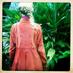 Embroideries at back of orange coat.