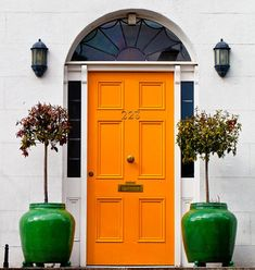Marigold front door with centered knob + emerald green ceramic planters