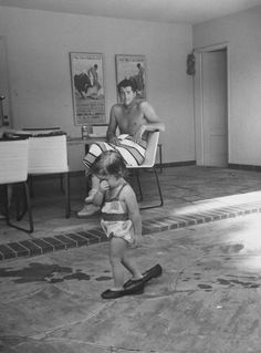 Dean Martin watches daughter Gina Caroline Martin walking in his shoes at their Beverly Hills home in 1958