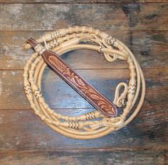 These George Moore style 32 Plait Romal Reins are natural rawhide color and handmade by one of the award winning braiders at Traditional Rawhide Braiders.
