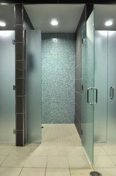 Classic fitness center showers with frosted glass doors and tile surround.