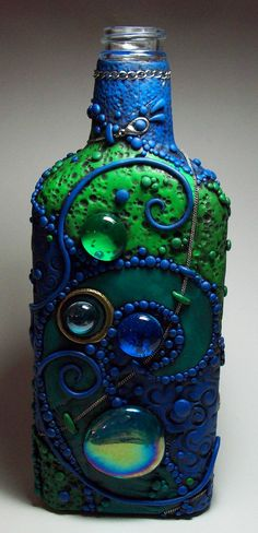 A glass flask decorated with polymer clay, found objects and glass gems.