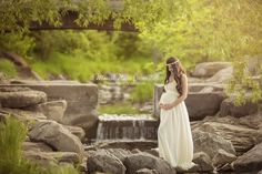 Beautiful outdoor maternity portrait in a creek with a waterfall