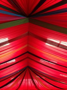 Bespoke carmine red drapes transform a barn venue into a series of Mexican waves! #partydecor