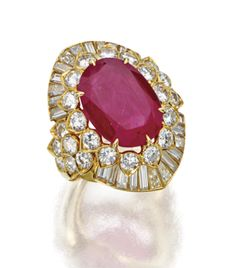 RUBY AND DIAMOND RING, VAN CLEEF & ARPELS, NEW YORK, CIRCA 1980.   The cushion-shaped ruby weighing 13.23 carats, bordered by 24 tapered baguette diamonds weighing 2.92 carats and 26 round diamonds weighing 3.27 carats, mounted in 18 karat gold, size 6½, signed Van Cleef & Arpels, numbered N.Y. 3622 S.O.