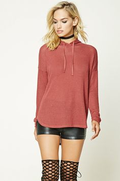 An open-knit sweater featuring a drawstring hood, long dolman sleeves, and a curved hem.