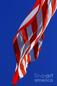 The underside of a flag swaying in the breeze with a crystal clear blue sky.