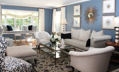 A grey, black and blue mansion living room idea with a glass table positioned in the middle of a room that has flowers and white animal decorations on top.