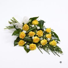 Classic Yellow Rose Sheaf. Elegant folded aspidistra and aralia leaves are nestled amongst large-headed yellow roses to create this stunning sheaf which is finished with delicate white September flower and foliage.
