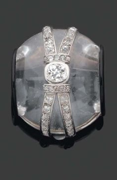 A rare and Important Art Deco rock crystal clip brooch, designed by SUZANNE BELPERRON, circa 1930. Centring a polished diamond, mounted in silver and platinum. Maker's mark for Gröene et Darde.
