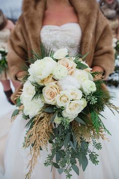 Winter bridal bouquet with white roses and evergreen sprigs. #WinterWedding #BridalBouquet #WeddingFlowers