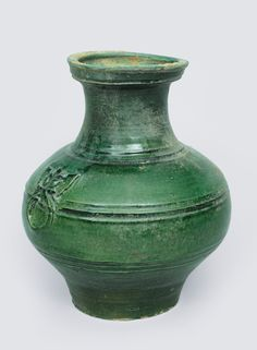 A shoulder pot with masks and ring handles  China, prob. Han period (206 bef. Chr. - 220 after Chr). Ceramic, reddish body dark green glazed. Bellied body with tapered stand. Sideways ring handles with animal masks. Unmarked, min. chipped. and little rest. H. 31 cm.