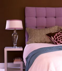 Purple upholstered headboard really pops against the chocolate walls
