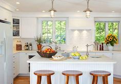 White kitchen cabinets with hardwood floors. Urban Archeology pendant lights.