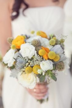 Gorgeousss. Craspedia, Succulents, and grey berries, mixed with fluffy white flowers and yellow flowers. Looks like there's some Dusty Miller and Baby's Breath in there, too.