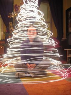Hold a strand of holiday lights from above with one end in your hand. Spin it in a circle from above. It'll make a cone/tree shape! via photojojo
