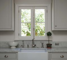 Tone on Tone - Beautiful kitchen with light gray shaker kitchen cabinets, white carrara marble countertops, farmhouse sink, French windows