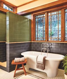 Tile in natural colors mirror the landscape that can be seen through the wall of windows that are cased in period-style woodwork.
