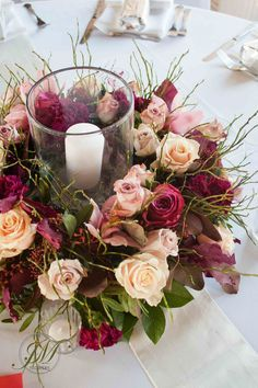 Burgundy and peach wedding table arrangements. A floral wreath with incorporated candle in a hurricane vase.