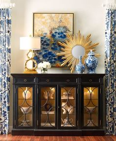 blue + white, blue + gold, curtain fabric, pottery, glass-front display cabinet, dark furniture, asymmetrical arrangement, big art, white flowers
