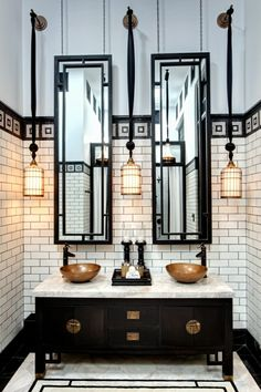 Black and white industrial 1920s Gatsby bathroom with white subway tiles, double vanity sink with brass accents wire pendant light