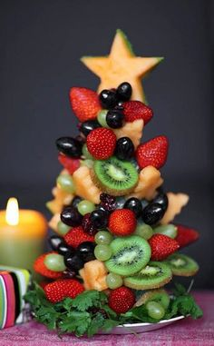 Fruit Christmas Tree Centerpiece ~~ Materials Needed:1 styrofoam cone (small or medium size), Toothpicks, Cookie cutters with various shapes (I used a gingerbread-man shaped and a star shaped cutter). Assorted fruits – I used green and black grapes, strawberries, kiwis, dried cranberries and a honeydew melon. Cilantro is the garnish / base.  Cilantro garnish.