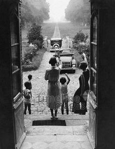 Abschied, 1930er. Zwei Frauen und drei Kinder stehen an der Haustür und winken zwei abfahrenden Autos nach. ullstein bild - ullstein bild/Timeline Images #Abfahrt #Abschied #Ausflug #winken #30er #1930er #Oldtimer