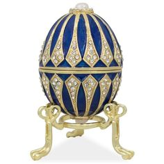 """3.25"""" Blue Enamel Jeweled Faberge Inspired Easter Egg - 3.25 Inches Tall - Enamel Gold Plated Pewter, Austrian Crystals - Hand Painted - Padded Satin Lined Gift Box - Imported You'll love the elegance of this Faberge inspired, blue hued, Easter egg. A graceful detachable display stand is included with this beauty. Fashioned from fine pewter. Then it is hand enameled by our skilled artisans. This sparkling egg is adorned with clear crystals and high-polished enamel with golden trim. It opens…"""
