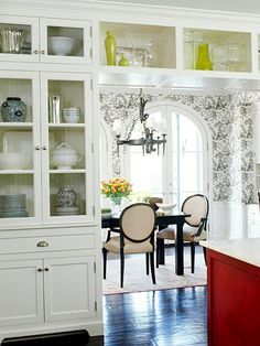 Pretty Glass doors to show off favorite serving pieces; would be nice in the dining room outlining the entry to the kitchen as well.  Good alternative to a traditional hutch.  I like how this goes above the doorway, too.