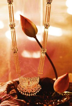 lotus necklace in gold by Tanishq with diamonds, rubies, emeralds and pearls.