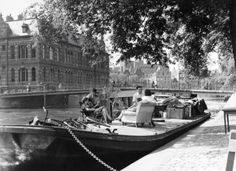 1940. Moving by barge on the canals of Amsterdam. People are sitting in the armchairs next to their household goods on the deck of barge at the Zwanenburgwal. Photo Spaarnestad. #amsterdam #1940 #zwanenburgwal