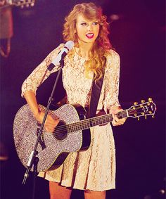 Taylor Swift. Super cute lace dress. Love her signature curls. Still love her sparkly guitar. This picture is perfect.