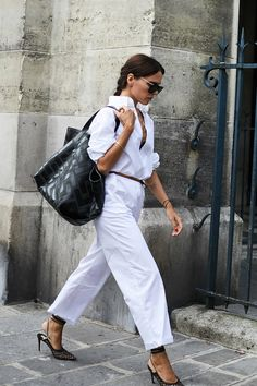 Evangelie Smyrniotaki in an all  white outfit (button down and pants) paired with black accessories.