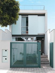 Facade of Narrow House with Green Gate Minimalist House Design, Small House Design, Minimalist Home, Modern House Design, Facade Design, Fence Design, Exterior Design, Compact House, Narrow House